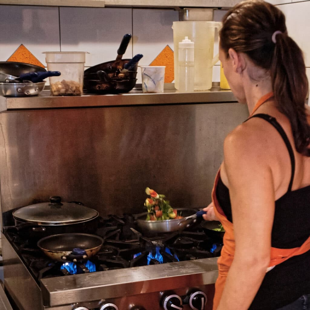 Photo of a woman cooking healthy food.